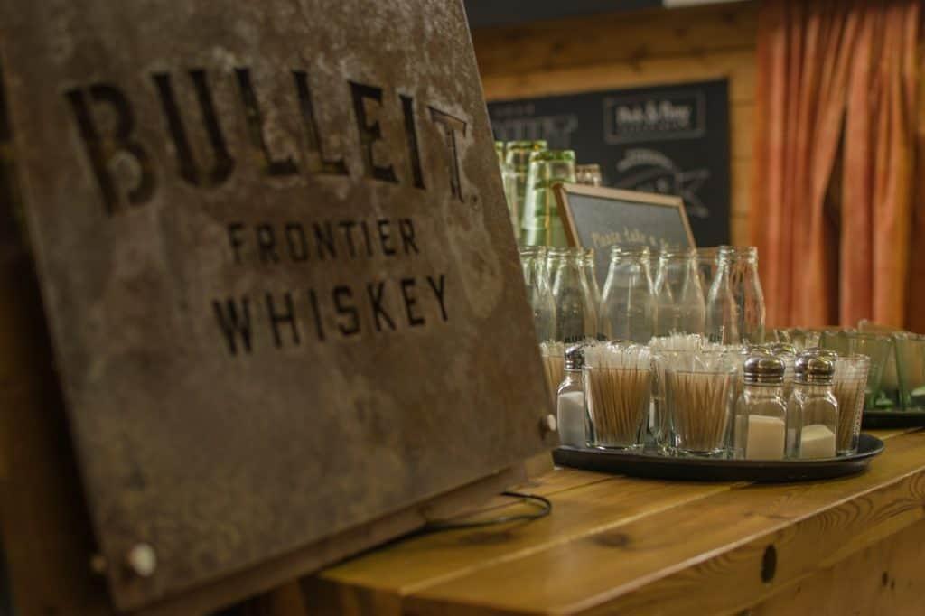 Imagem de bandeja repleta de saleiros e paliteiros sobre bancada de bar