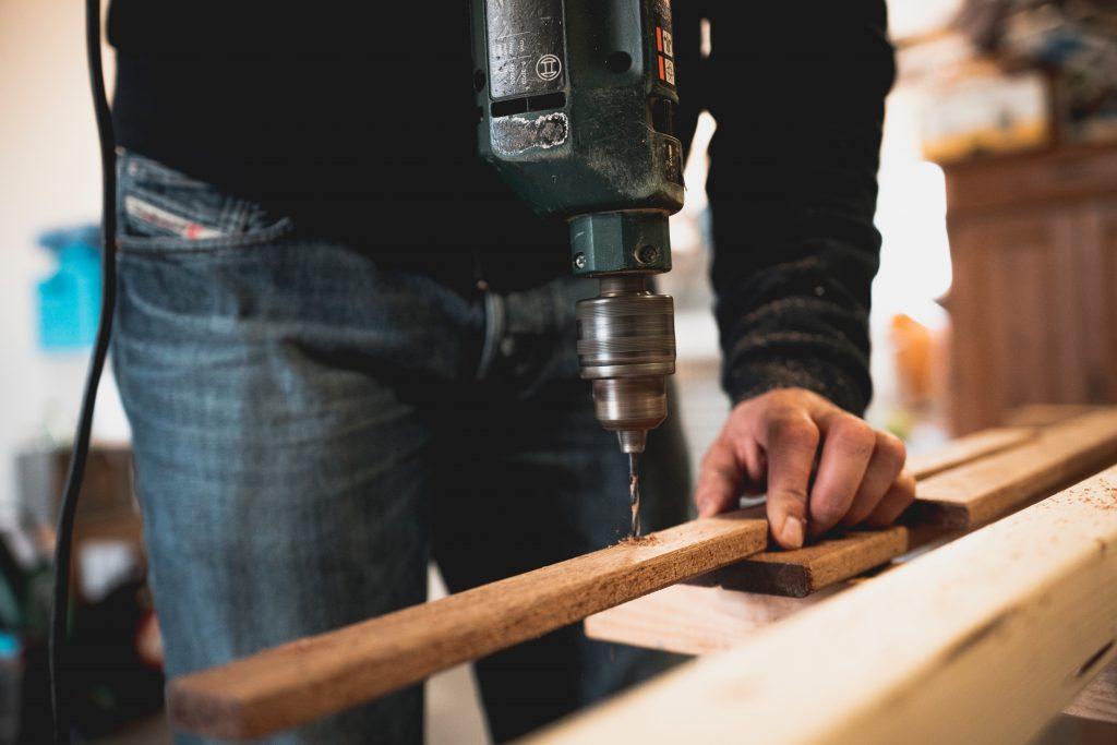 Imagem mostra um homem usando uma furadeira Bosch em uma peça de madeira.