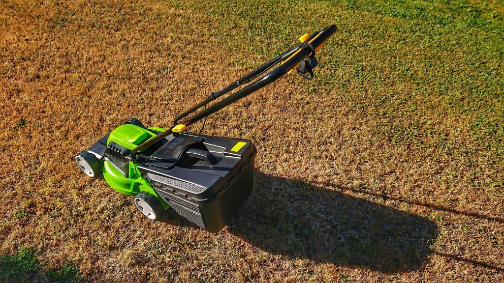 Imagem mostra um cortador de grama em descanso sobre a relva.