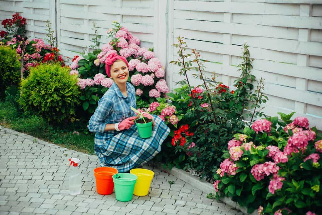 Na foto uma mulher em frente a um jardim com alguns cachepots ao lado.