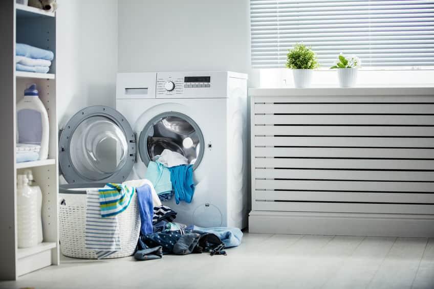Na foto uma máquina de lavar com algumas roupas em uma lavanderia.