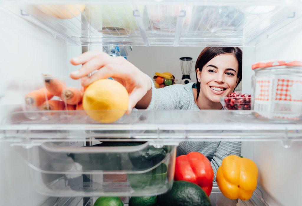 Mulher pegando uma fruta dentro da geladeira.