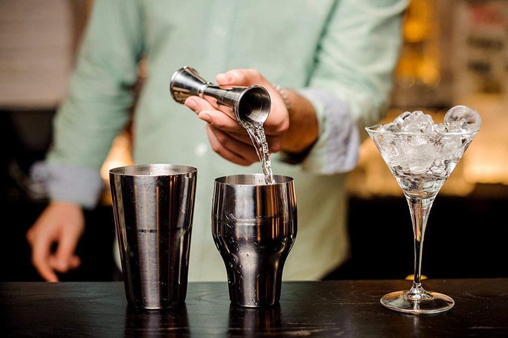 Uma pessoa vira um dosador, que por sua vez despeja um líquido claro dentro de um copo, no centro da mesa.
