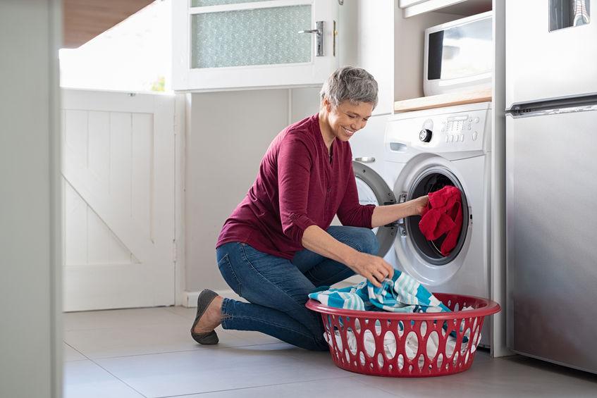 Na foto uma mulher colocando roupas dentro de uma lavadora.