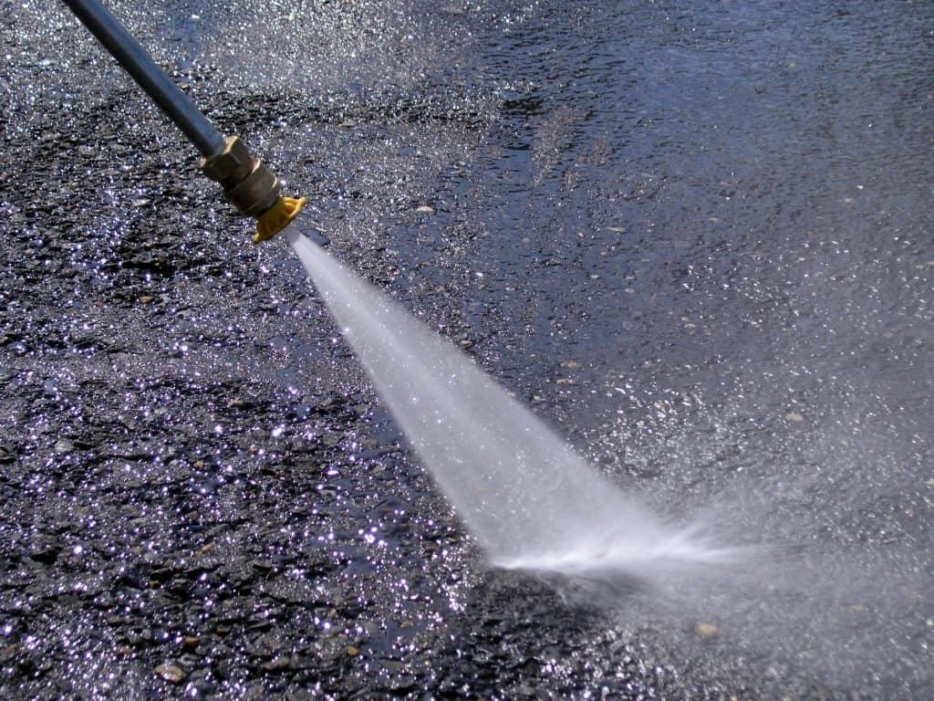 Imagem mostra uma lavadora de alta pressão e seu jato de água contra o asfalto.