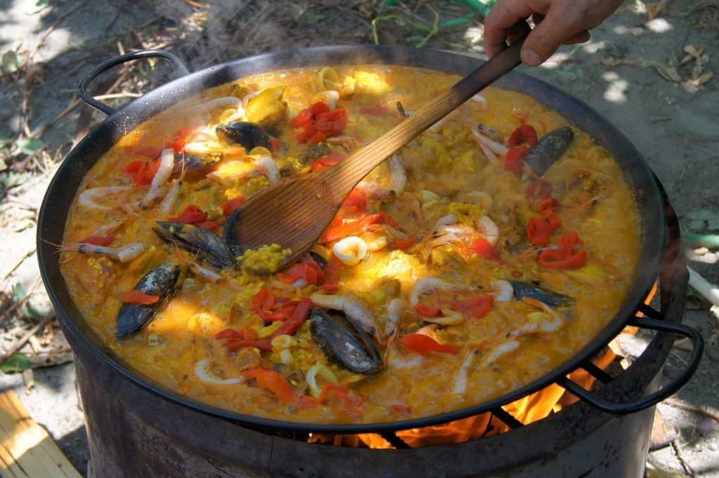 Imagem de pessoa preparando paella de frutos do mar usando colher de arroz de madeira.