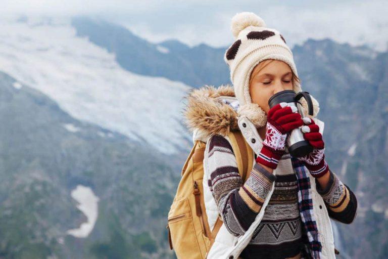 Na foto uma menina com roupas de frio bebendo uma bebida em um copo térmico com montanhas ao fundo.
