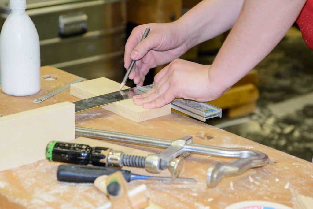 imagem das mãos de uma pessoa usando um esquadro para marcar uma peça de madeira em uma oficina