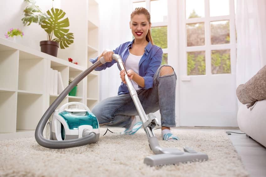 Na foto uma mulher aspirando um tapete em uma sala de estar.