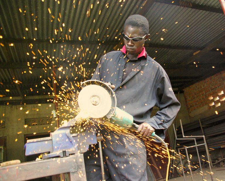 Imagem mostra um homem trabalhando com uma grande esmerilhadeira.