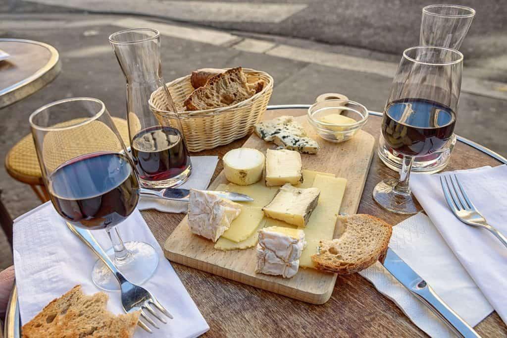 Na foto uma tábua com queijos e algumas taças de vinho.