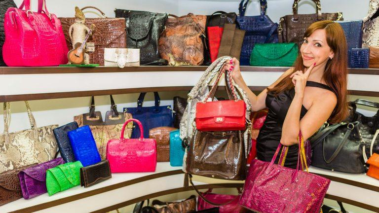 Mulher escolhe bolsas de grande acervo