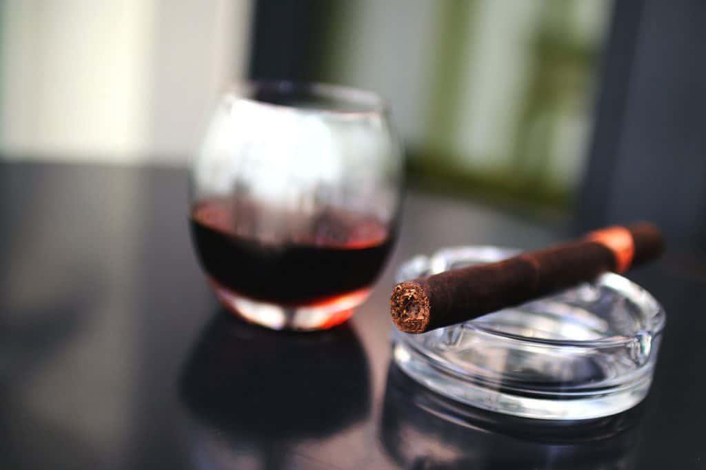 Um cinzeiro, um charuto e um copo com conhaque.