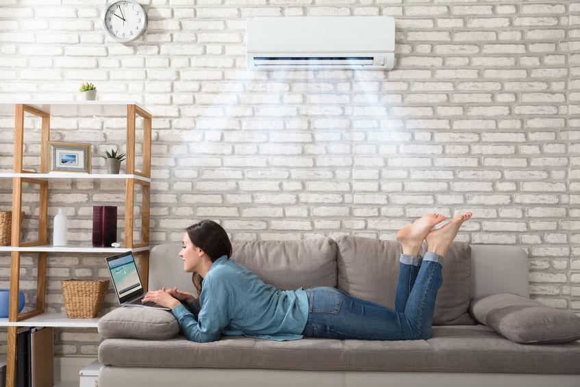 Uma mulher relaxada em uma sala residencial com um ar-condicionado LG instalado no teto.
