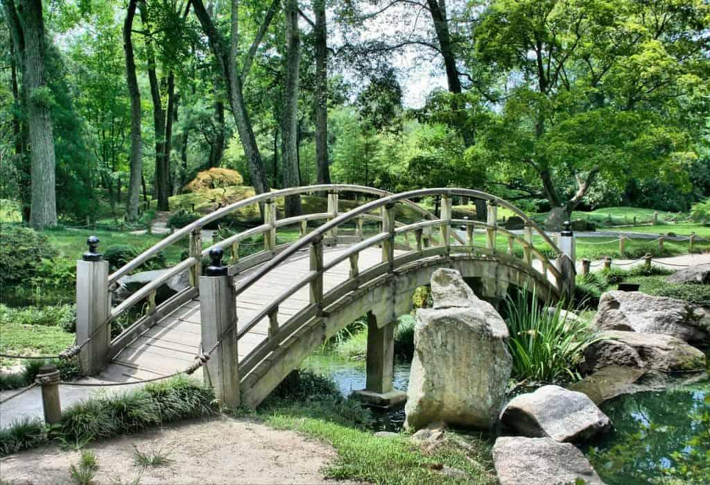 Na foto um jardim, com um lago e uma ponte.