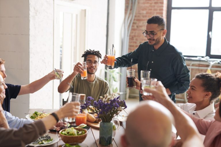 Na foto algumas pessoas em uma mesa brindando.