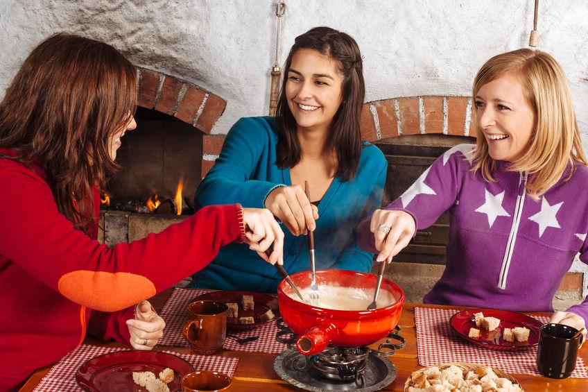 Imagem de três mulheres compartilhando uma refeição de fondue de queijo em réchaud de cerâmica