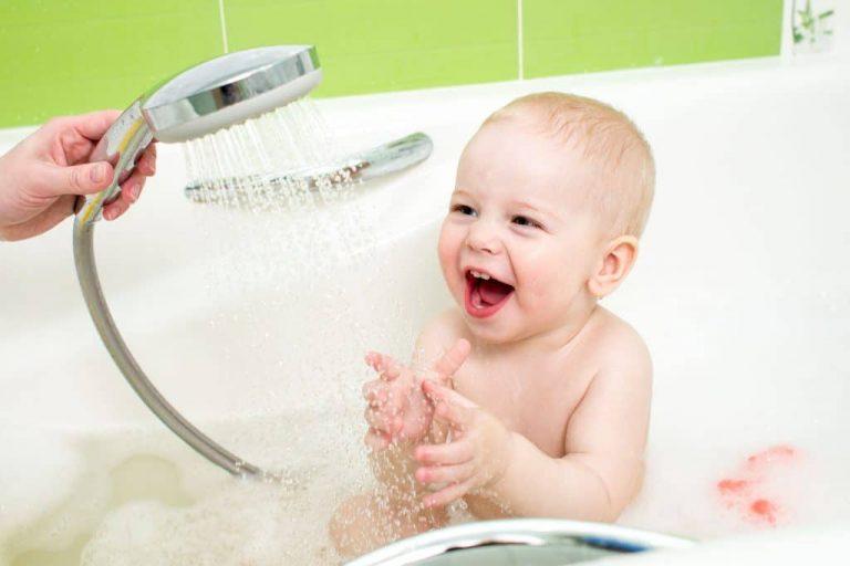 Na foto um bebê dentro de uma banheira.