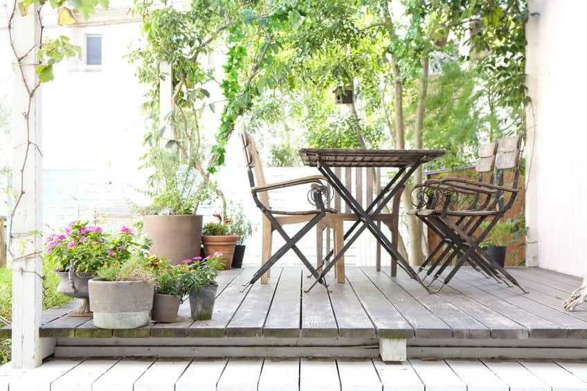 Imagem de mesa com quatro cadeiras em jardim.