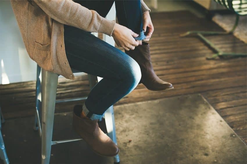 Imagem pessoa sentada em uma banqueta de plástico cinza ajeitando a barra da calça jeans.