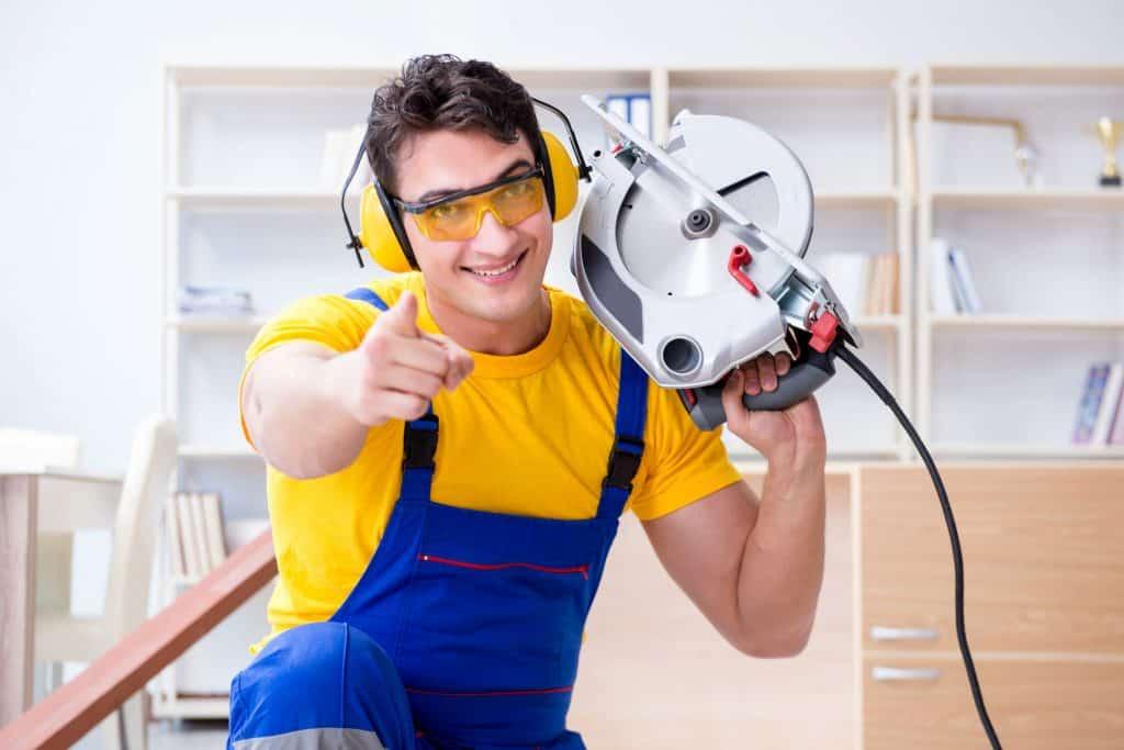 Um homem com uma serra elétrica circular em uma das mãos. Ele veste um macacão azul, óculos de proteção e uma camiseta amarela. Ele aponta o dedo indicador da mão sem a serra.