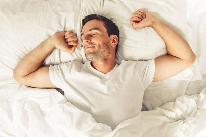 homem despertando se espreguiçando na cama, ele está vestindo branco e coberto por um edredom branco