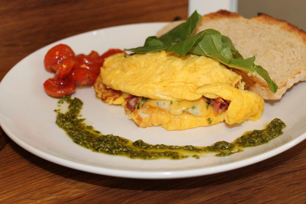 Prato com omelete, pão e outros acompanhamentos
