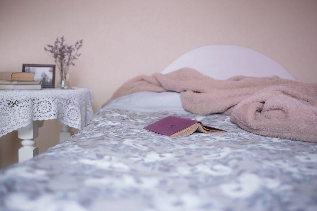 Imagem de cama de solteiro com roupa de cama estampada, coberta em tecido cor de rosa e livro. Ao lado há uma mesa lateral branca com outros livros dispostos.