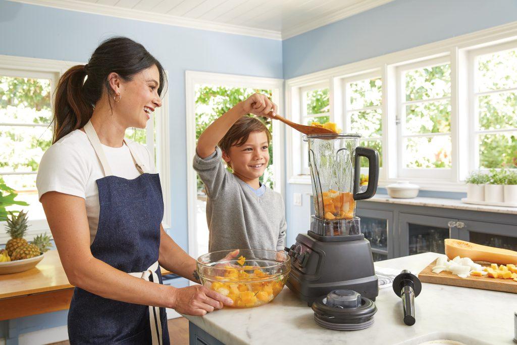 Na foto uma mulher e um menino em uma cozinha usando um liquidificador.