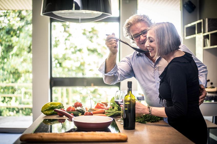 Casal de idosos cozinhando juntos em linda e moderna cozinha.