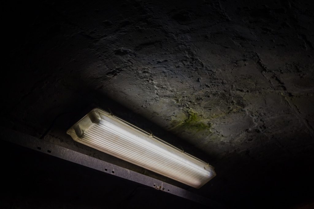 Imagem de duas lâmpadas tubulares em suporte metálico com proteção de plástico em um túnel