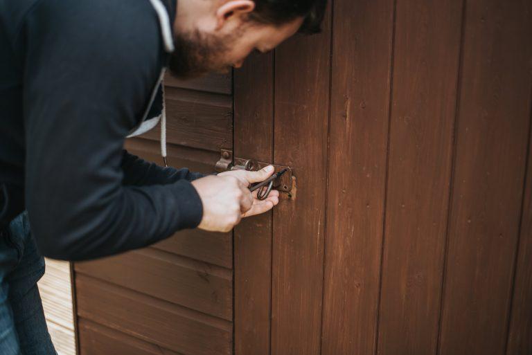 Imagem mostra um homem arrombando uma fechadura de uma porta de madeira.