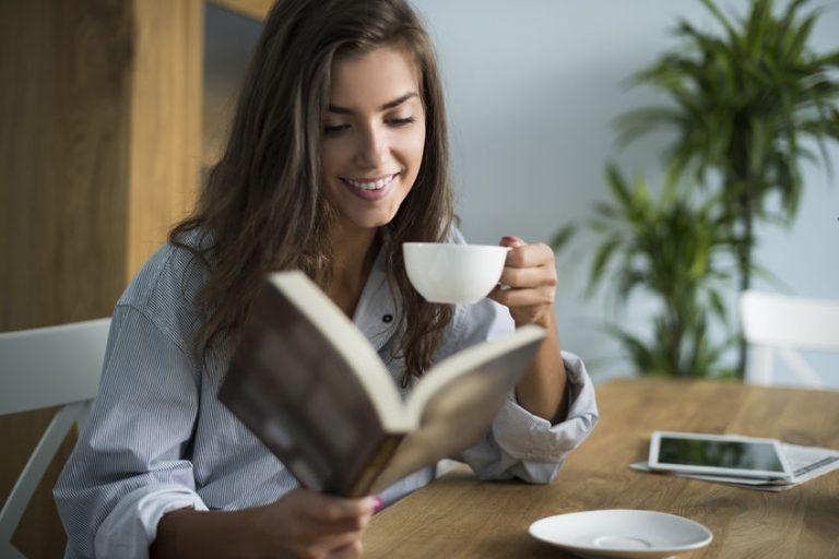 Mulher bebendo café e lendo livro na mesa.