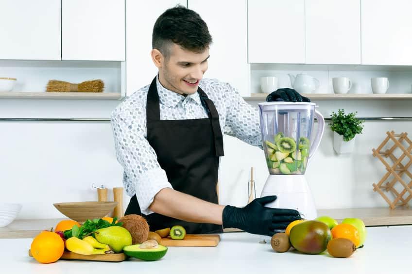 Na foto um homem preparando um suco no liquidificador.