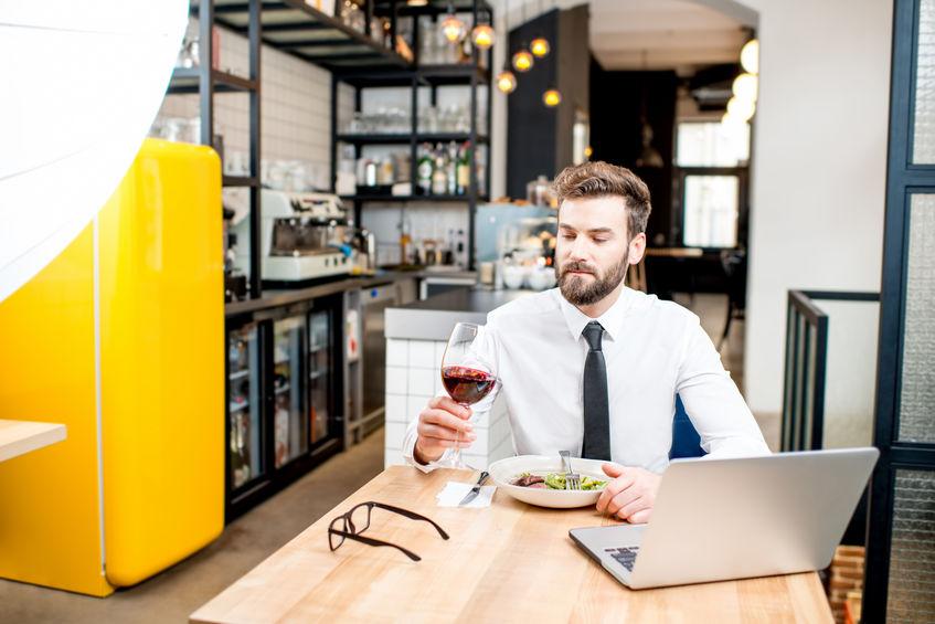 Rapaz sentado à mesa com taça de vinho e adegas em cozinha ao fundo