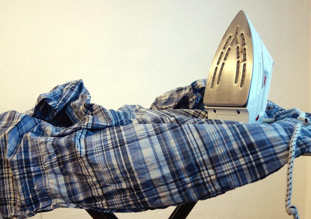 Imagem de ferro sobre roupa de cama e tábua de passar