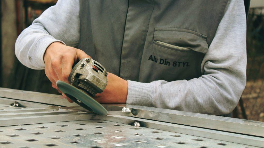 Imagem mostra uma pessoa usando uma esmerilhadeira em uma peça de metal.