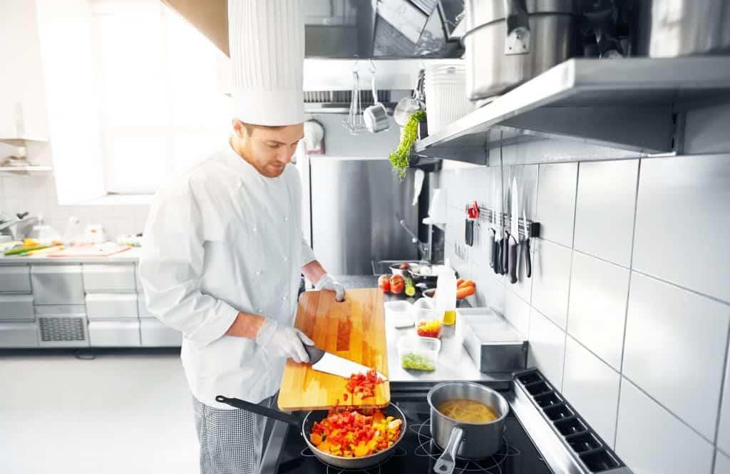 Chef prepara receita em cozinha industrial equipada com barra magnética para guardar facas.