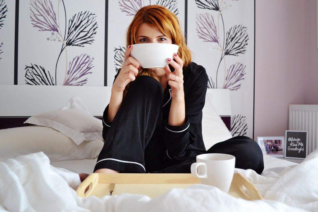 Imagem de mulher tomando café da manhã na cama