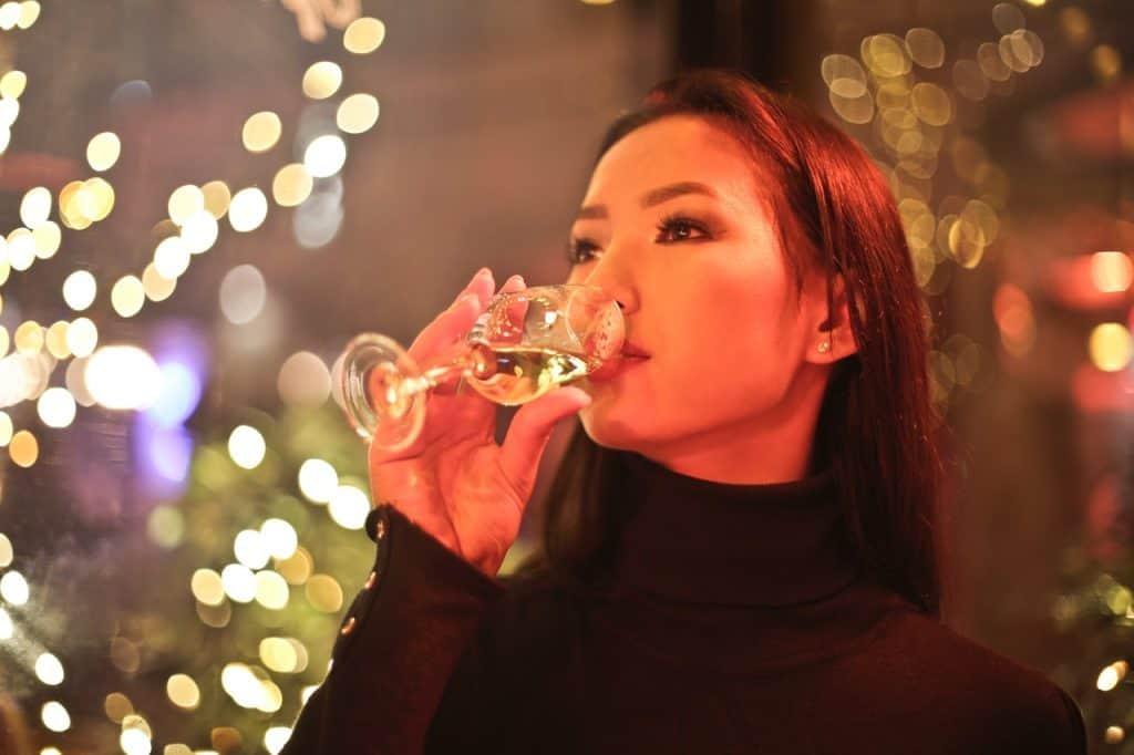 Foto de uma mulher oriental, com blusa de gola alta preta, bebendo espumante em uma taça de champagne. Ao fundo, luzes em blur.