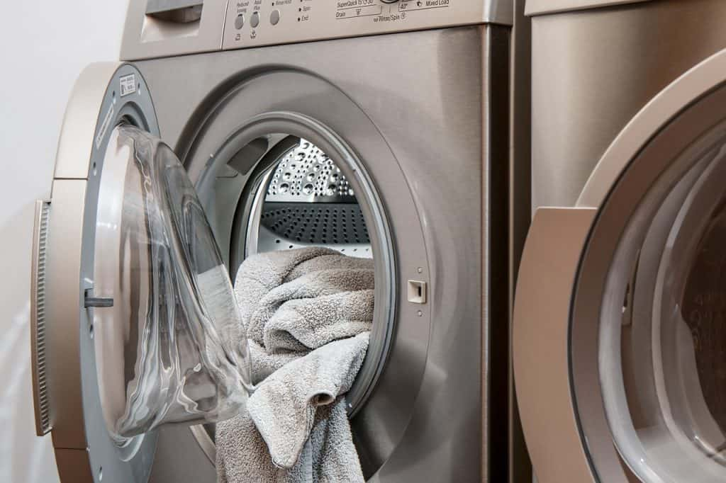 Imagem de máquina de lavar com tampa frontal aberta e uma toalha cinza sendo colocada dentro.