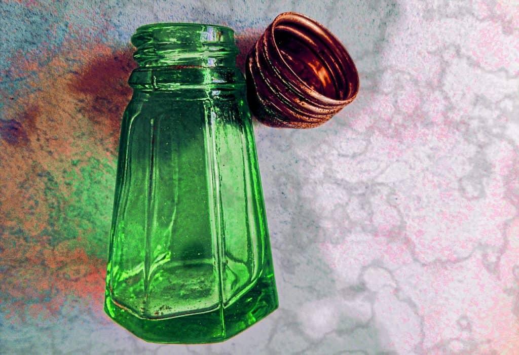 Imagem de um saleiro de vidro verde deitado e destampado. Ao lado, está sua tampa.