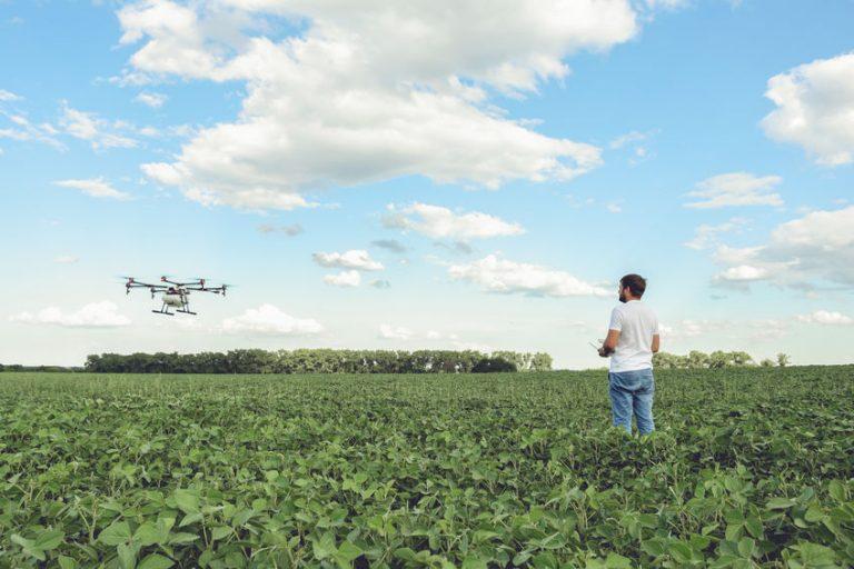 Imagem mostra um homem controlando um drone em um grande campo com vegetação.
