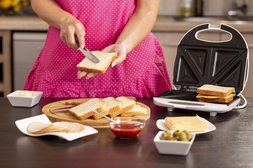 Imagem de mulher de avental cor de rosa passando manteiga em pão durante o preparo de lanche para a sanduicheira