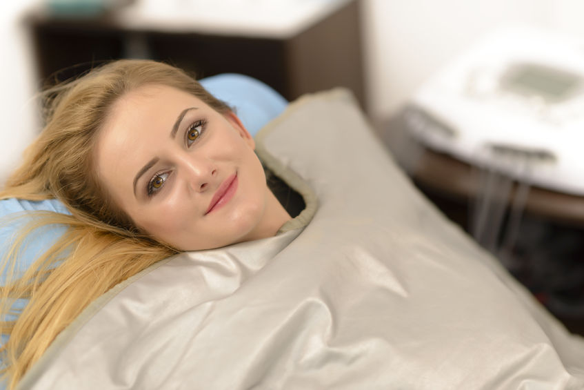 Imagem de mulher fazendo tratamento estético com manta térmica