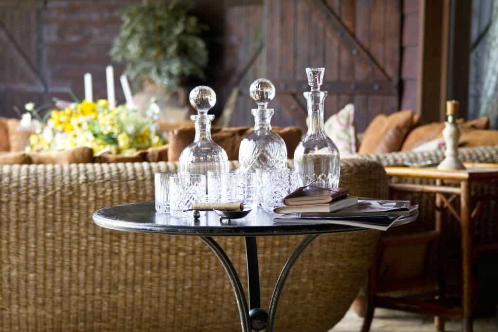 Imagem de mesa de canto de madeira com bebidas em cima.