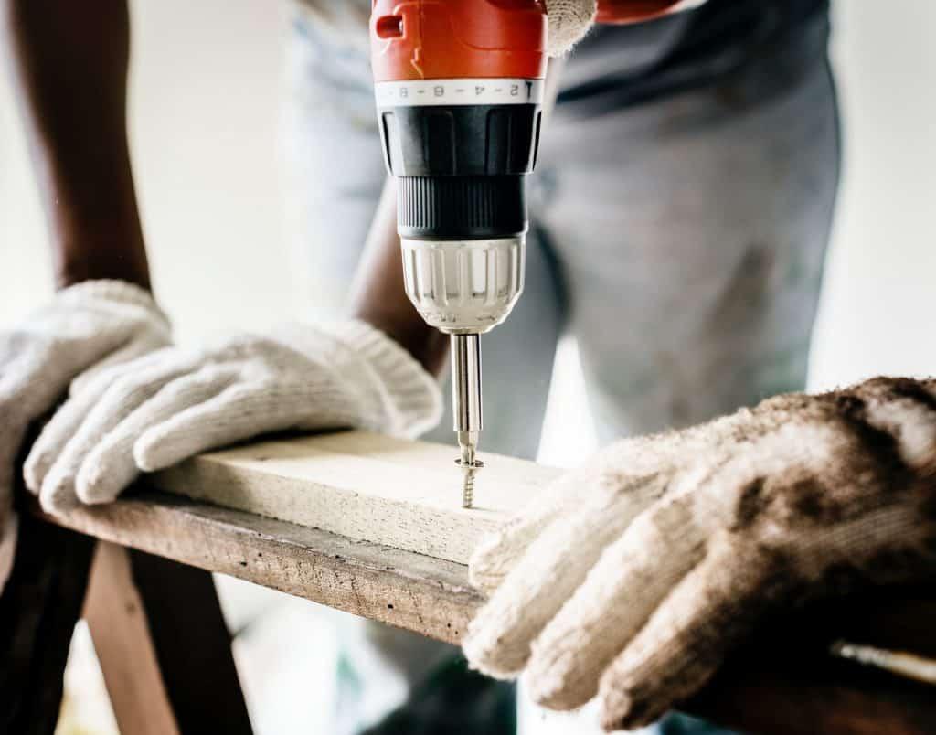 Imagem mostra uma mini furadeira ajudando a reparar uma tábua de madeira.