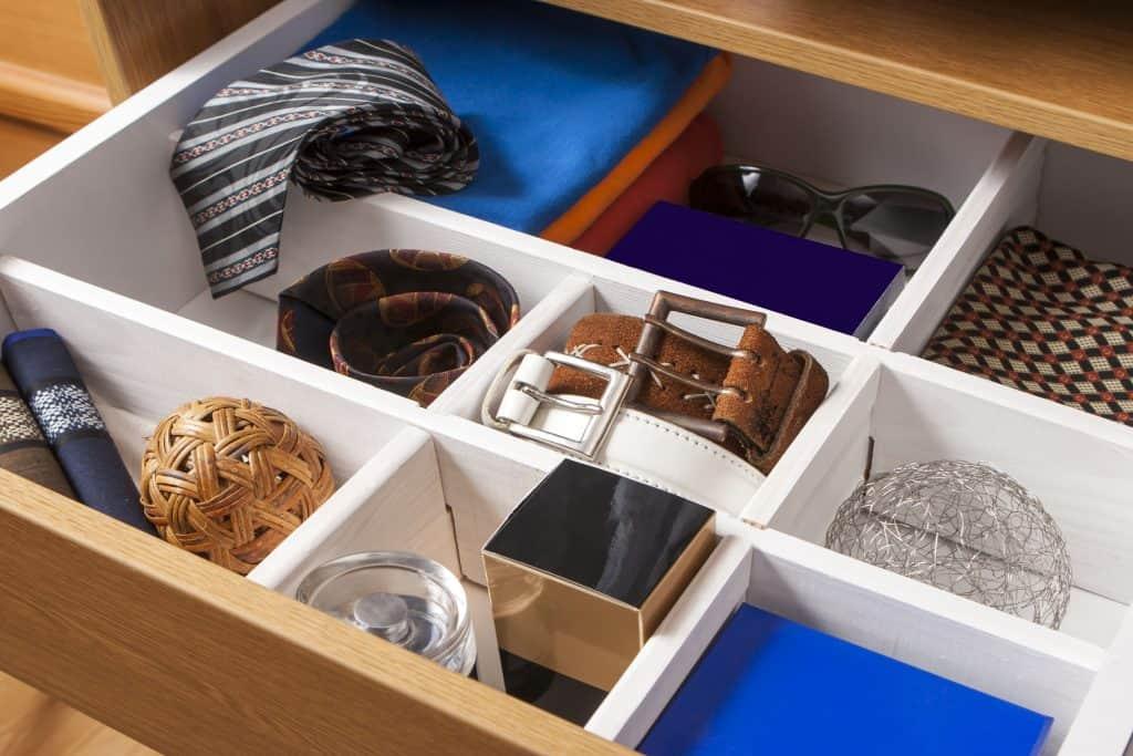 Roupas, acessórios, cintos, gravatas e documentos em dispostos em um mesmo organizador de gaveta.
