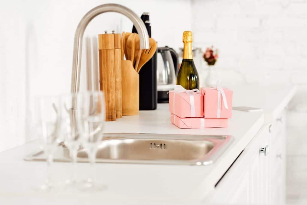 Foto que mostra taças de champagne em cima da pia.