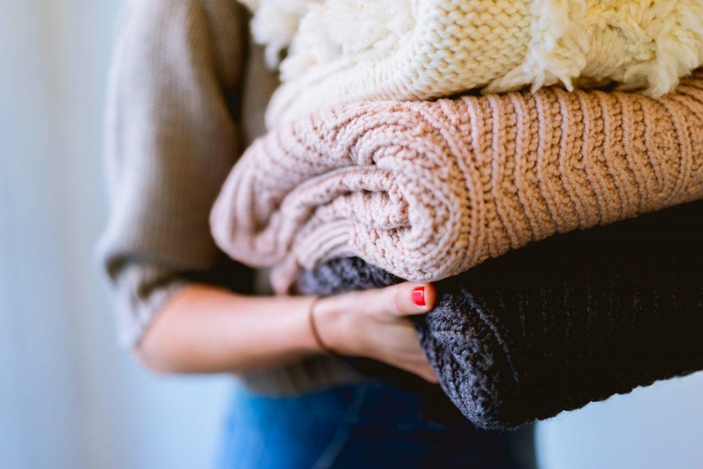 Na foto uma mulher carregando três cobertores dobrados.